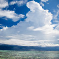 Dramatic white cumulus cloud formation towering over the coastline and ocean in a blue sunny sky Stock Photography
