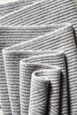 Draped melange gray woolen knitted fabric as background. Royalty Free Stock Photo
