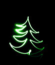 Drawing christmas tree by flashlight in the air Stock Images