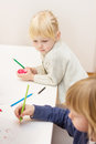 Drawing with colorful crayons little girl looking her brother Stock Photos