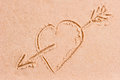 Drawing heart with an arrow on the wet sand a Stock Photography