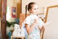Drawing lesson portrait of a girl standing next to his easel a Royalty Free Stock Photos