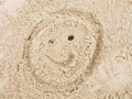 Drawn smiley face in summer beach sand. Painted head in dray salt sand. Royalty Free Stock Photo