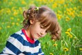 Dreaminess portrait of thoughtful little girl on the background lawn with dandelions Royalty Free Stock Photography
