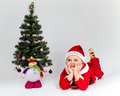 Dreaming baby boy dressed as santa claus lying next to christmas tree white background Royalty Free Stock Photos