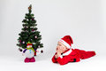 Dreaming baby boy dressed as santa claus lying next to christmas tree white background Stock Images