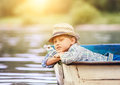 Dreaming boy lying in old boat on the river Royalty Free Stock Photo