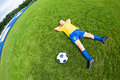 Dreaming boy soccer player lying on natural grass fish eye lens Royalty Free Stock Photo