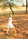 Dreaming girl walking barefoot in dead leaves barefooted blue skirt and whit t shirt and on autumn Stock Image