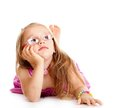 Dreaming little girl laying on floor isolated portrait of a in glasses over white Royalty Free Stock Images