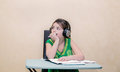 Dreaming little pretty girl sitting behind a table and looking away with a headphones on her head concentrated thinking against an Royalty Free Stock Images
