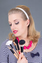 Dreaming pinup woman with make up brushes over grey Royalty Free Stock Photography