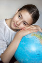 Dreaming thoughtful girl with blue round globe schoolgirl Royalty Free Stock Photography