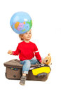 Dreaming to vacation child with open eyes and looking at world globe in motion and sitting on luggage against white background Stock Image