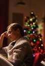 Dreaming woman sitting in armchair in front of christmas tree young Royalty Free Stock Image