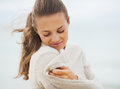 Dreaming young woman wrapping in sweater on coldly beach Royalty Free Stock Photo