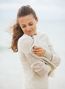 Dreaming young woman wrapping in sweater on coldly beach with long hair Royalty Free Stock Photo