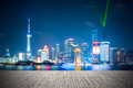 Dreamlike city background of shanghai skyline at night light show with wooden floor prospect Royalty Free Stock Photos