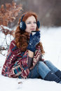 Dreamly young red-haired woman drinking a hot drink from a mug in the winter park. Royalty Free Stock Photo