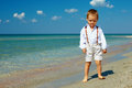 Dreamy baby boy stands in surf on sea beach Stock Images