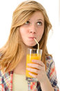 Dreamy blonde girl sipping orange juice in plaid shirt Royalty Free Stock Photo
