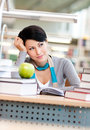 Dreamy female student studies at the reading hall Royalty Free Stock Photo
