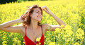 Dreamy girl enjoying the nature on a sunny day in the flowering yellow field Stock Photo