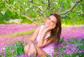 Dreamy girl in spring garden portrait of nice sitting down on pink flowers field apple tree watching for first blossom beauty of Royalty Free Stock Photo