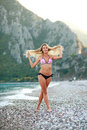 Dreamy girl walking on summer sea beach in bikini Royalty Free Stock Photo