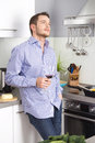 Dreamy happy well looking man drinking red wine in the kitchen Royalty Free Stock Image