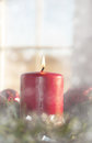 Dreamy image of a red christmas candle burning inside wreath with window on background Stock Image