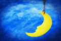 Dreamy moon hanging on string with night sky background.