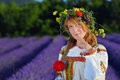 Dreamy peasant girl in a flowers wreath dressed in a russians gown stands in lavender field Royalty Free Stock Photography