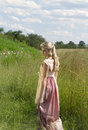 Dreamy portrait of bohemian blonde girl in field of grass color a beautiful wearing romantic dress hairstyle and necklace walking Royalty Free Stock Photo