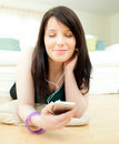 Dreamy woman listening music lying on the floor Royalty Free Stock Photo