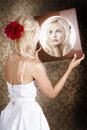 Dreamy woman looking at mirror reflection indoor portrait of a blond vintage lady Royalty Free Stock Photography