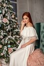 A dreamy young beautiful girl in a white evening dress against a Christmas tree background Royalty Free Stock Photo