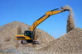 Dredge loads a rubble against the blue sky Royalty Free Stock Photo