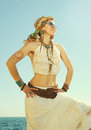 Dressed in boho chic style woman portrait, sunny  outdoor photo against sea Royalty Free Stock Photo