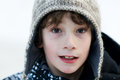 Dressed for the cold close up of an eight year old boy wearing a wooly winter hat outdoors in snow Stock Photo