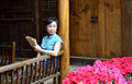 Dressed in traditional chinese costume woman was reading a book sitting front of the old house and read Royalty Free Stock Photos