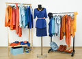 Dressing closet with complementary colors blue and orange clothes wardrobe full of all shades of an arranged on hangers shoes Stock Photo