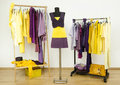 Dressing closet with complementary colors violet and yellow clothes wardrobe purple arranged on hangers an outfit on a mannequin Royalty Free Stock Photos