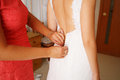 Dressing up the bride on wedding day mother helping young beautiful to get dressed for ceremony photographed Royalty Free Stock Photography