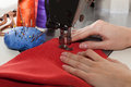 Dressmaker hands sewing a dress with red material Stock Photography