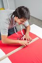 Dressmaker measuring red fabric young male a with ruler on table Royalty Free Stock Photo