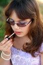 Dressy teen applies lipstick Stock Photos