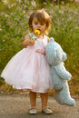 Dressy two year old girl in pink dress holding stuffed bear and flower cute multi racial wears a pale full holds a blue looks at a Stock Photography