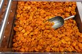 Dried apricots with a large metal spoon / scoop ready to be sold unpackaged to the environmentally conscious customers in a zero