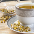 Dried camomile flowers surrounding fresh up of camomile tea Stock Photos